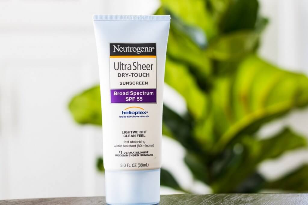 neutrogena ultra sheer sunscreen lotion in front of green plant