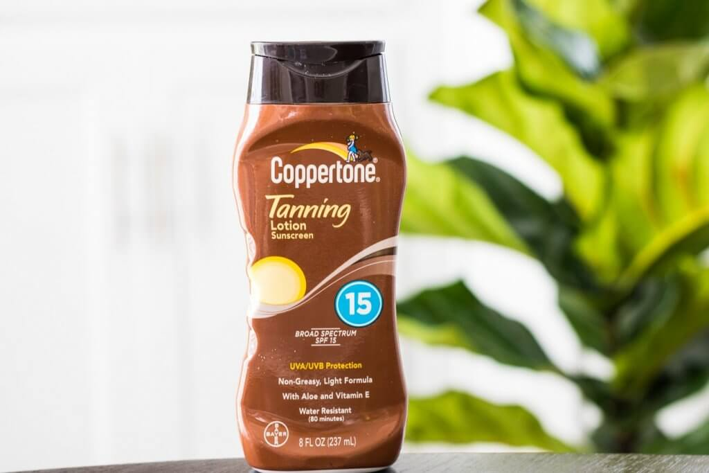 coppertone tanning lotion SPF 15 in front of green plant